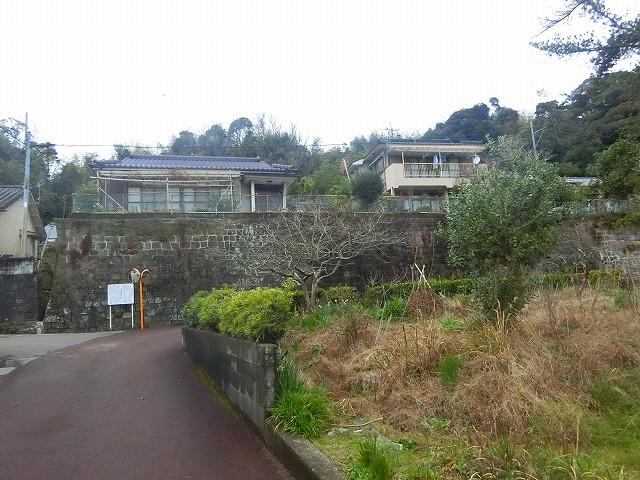 仮屋跡の壁の向こうの山が串木野城。