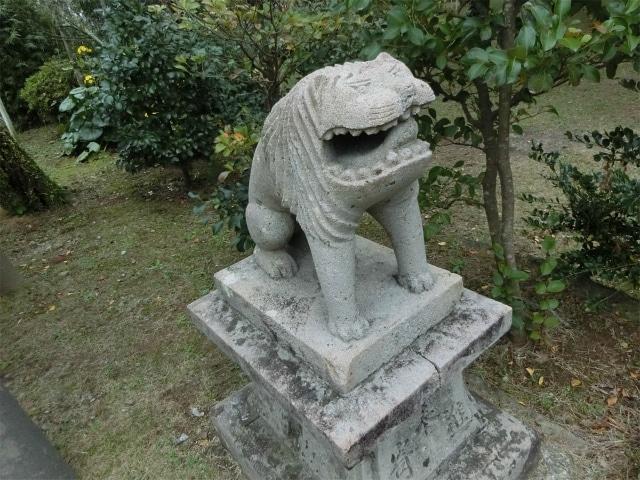 デカイ口の狛犬が何かをくわえています。